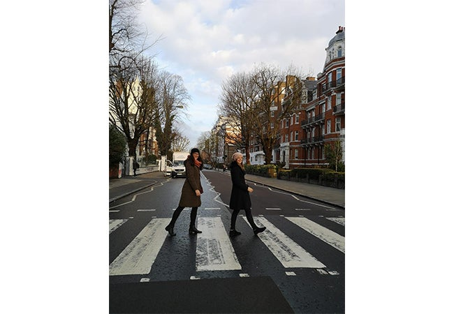 Business graduate student Alyssa and a friend cross the iconic Abbey Road intersection on a brisk day.