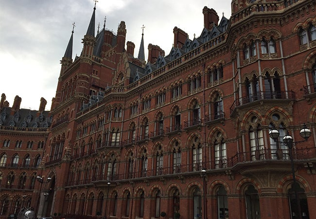 The ornate exterior of St. Pancras railway station is shown on an overcast day in central London.