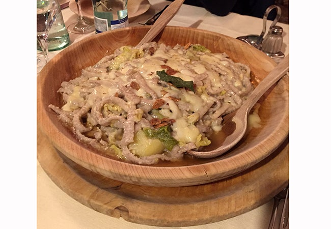 A close-up of a dish called pizzoccheri served in a wooden bowl with a wooden spoon.