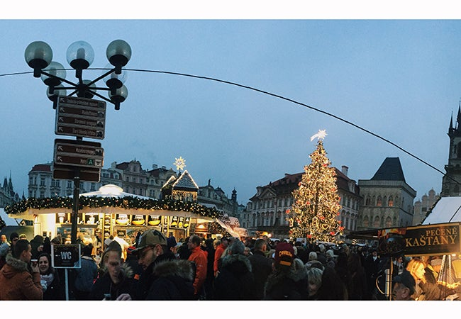 Shoppers peruse wares at a Christmas market adorned with holiday lights in Prague during the early evening.