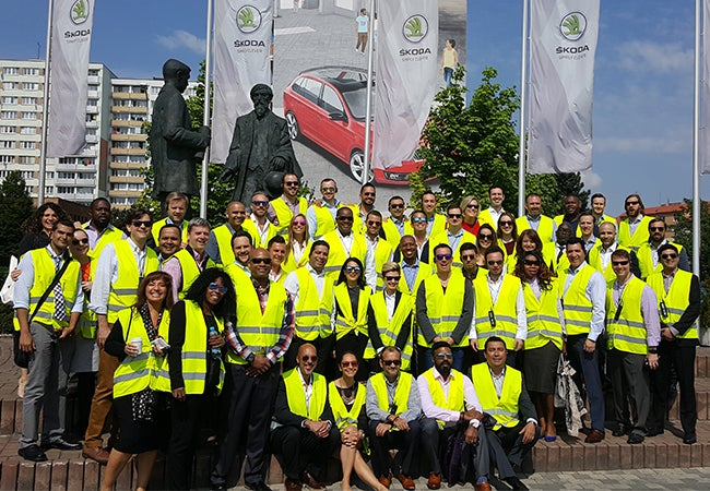 Students wearing yellow safety vests gather for a group photo in front of a statue in Prague.