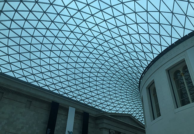 The curved glass ceiling of a building is made up of many triangular panels.