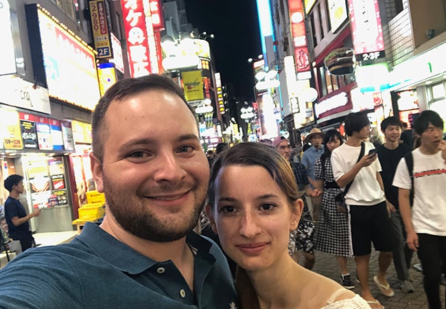 Ryan and his girlfriend take a selfie on a busy street at night, surrounded by pedestrians and lighted signs.
