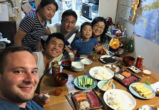Ryan takes a selfie with five members of his host family around the kitchen table in their home before dinner.