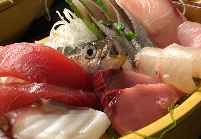 A close-up photo shows raw fish of various colors and types piled on top of one another.