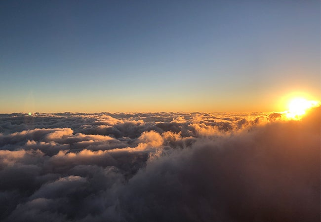 A scenic photo shows a calm blue sky above the clouds as the sun sets or rises in the distance.