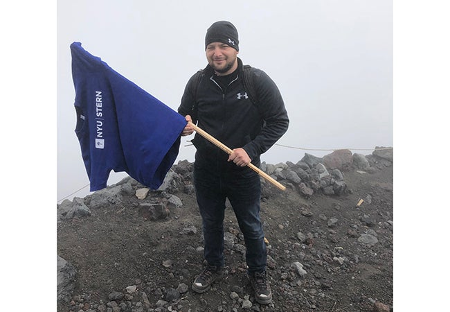 Ryan McClaskey holds a stick with an NYU t-shirt draped over the end like a flag while hiking on a chilly day.