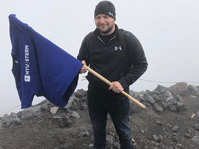 Ryan McClaskey holds a stick with a Stern t-shirt hanging to the end like a flag while hiking outdoors.