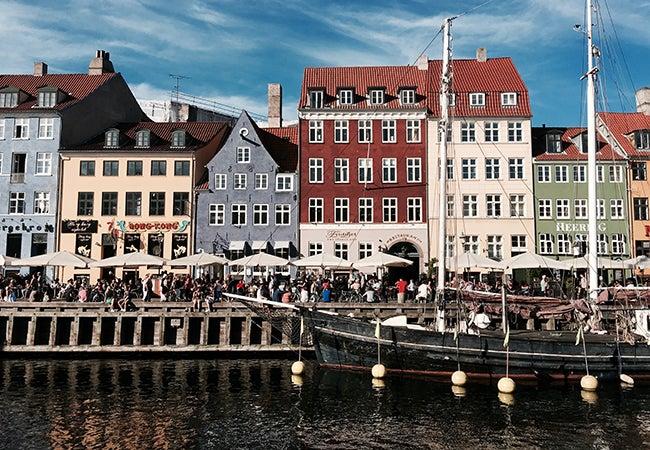 Pedestrians make their way through a row of white tents along a waterway in Copenhagen.