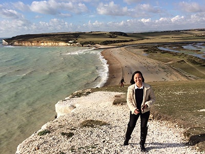 MBA student Kimberly Rodriguez smiles and stands beside a teal sea while studying abroad in London.