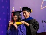 A student graduating and a faculty member