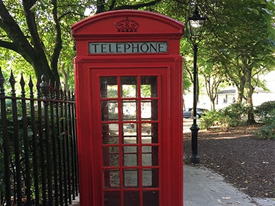 A bright red telephone booth stands empty next to a tall iron fence in a park in London.