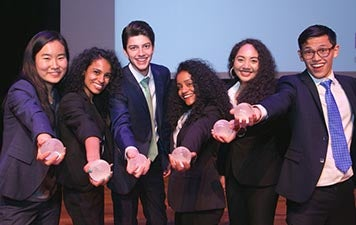 The six students who won the ISP Competition hold out their globe-shaped trophies on the Skirball stage.
