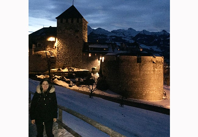 MBA student Ashley Grand stands in front of a small stone building during her travels while studying abroad.