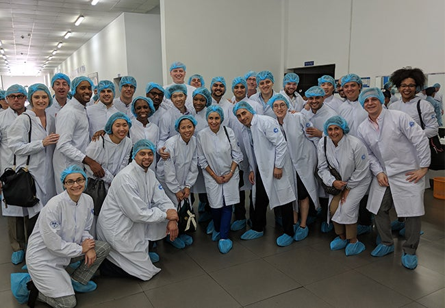 Executive MBA students don protective white coats, plastic hair nets, and blue shoe covers during a facility tour in Vietnam.