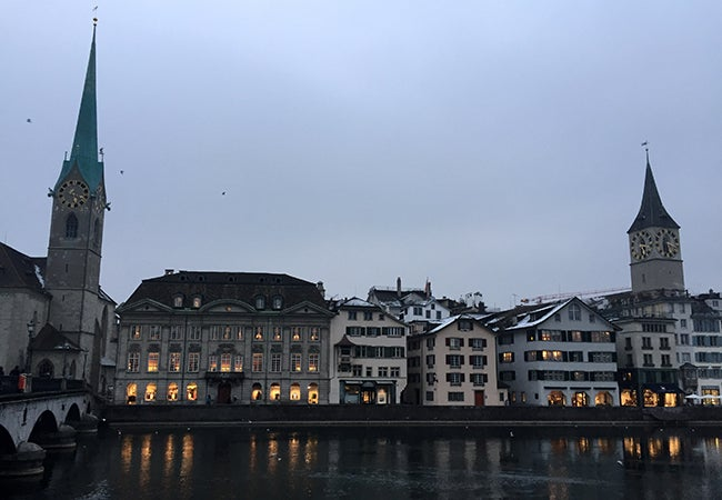 Evening sets on buildings in Zurich, framed by a tall green steeple.
