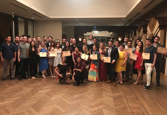 MBA students in Argentina hold up certificates or plaques following an indoor ceremony in Argentina.