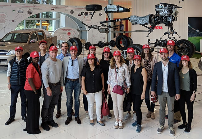 MBA students and trip leaders wearing red hats visit a Toyota facility while in Buenos Aires.
