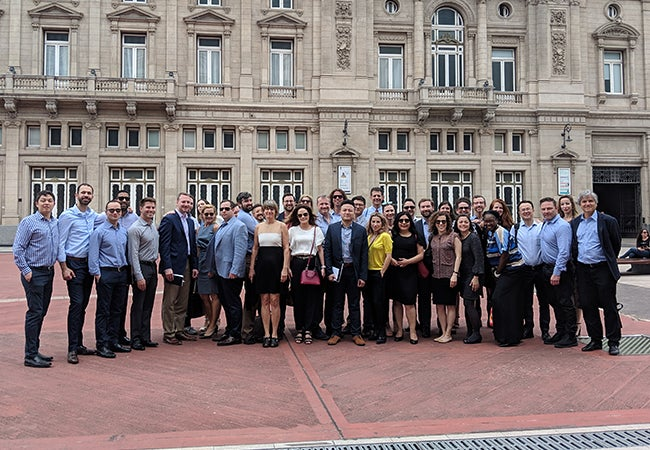 MBA students pause for a group photo outside of a large stone building in Buenos Aires.