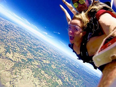 MBA student Cara Witt-Landefeld looks at the camera while skydiving with a partner in Australia.