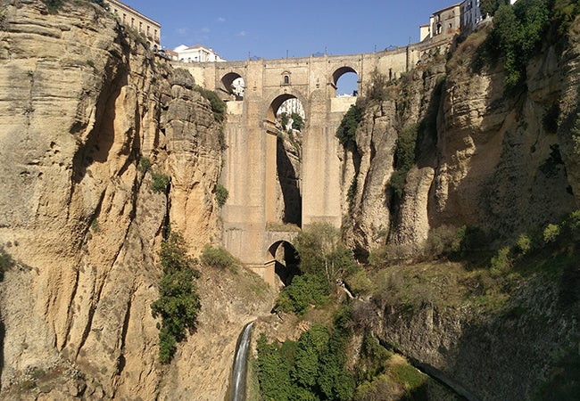 An ancient aqueduct built into a stone hillside towers above a small stream on a clear day.