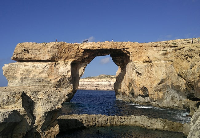 Visitors cross over a large stone arch surrounded on three sides by cliffs and water on a bright, sunny day in Malta.