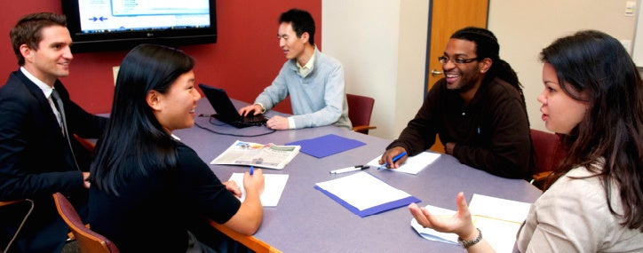 Students work on a group project in a group study room at Stern.