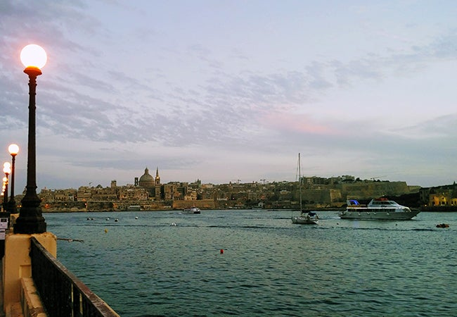 A seaside view of Malta shows small boats before a low-slung city of stone buildings in the distance.