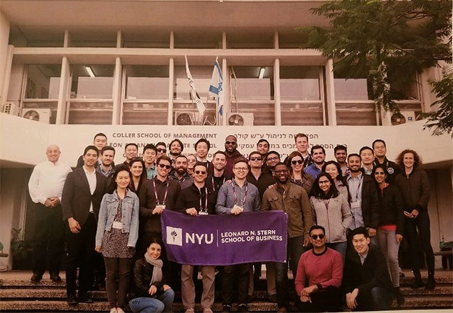 A group of MBA students hold a purple banner emblazoned with Stern's logo while standing on the stairs outside of a classroom building.