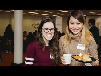 Two student smiling and posing with food