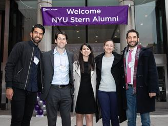 Alumni in front of Welcome NYU Stern Alumni sign in Gould Plaza
