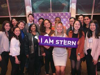 "Dean Menon and students posing with an ""I Am Stern"" banner"