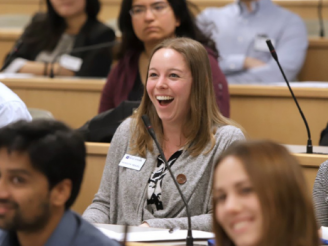 Woman in classroom with other students smiling