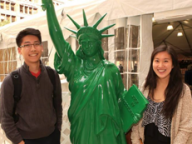 Students next to a replica of Statue of Liberty