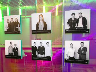 Colorful glass wall with photographs of students and NYU startup teams