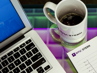Laptop, NYU Stern mug, and notepad