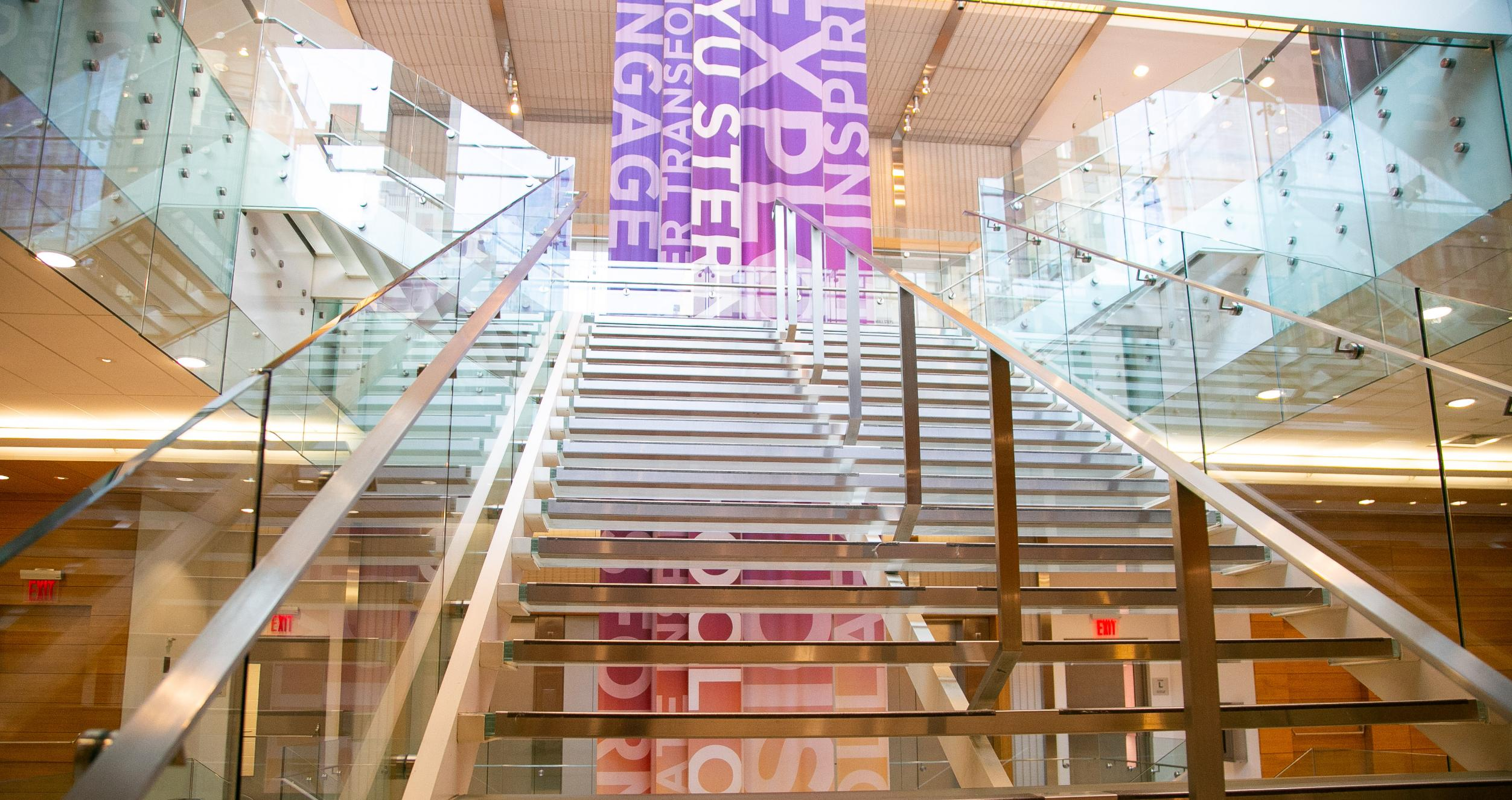 View from the bottom of a modern-looking glass stairway with a multi-colored banner behind it, located in Tisch Hall.