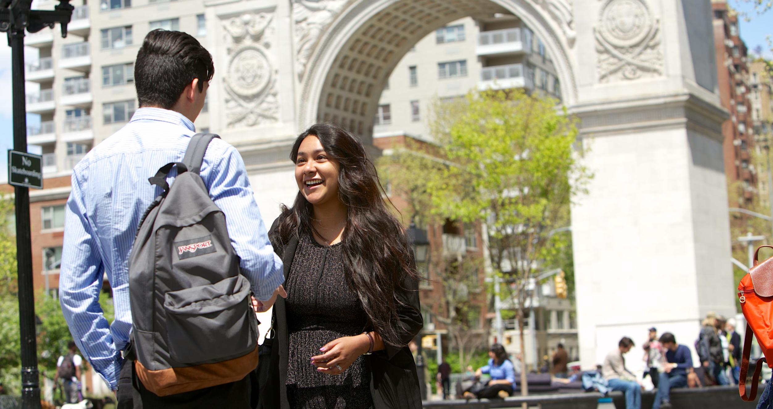 Students chat in front of the arch at Washington Square Park
