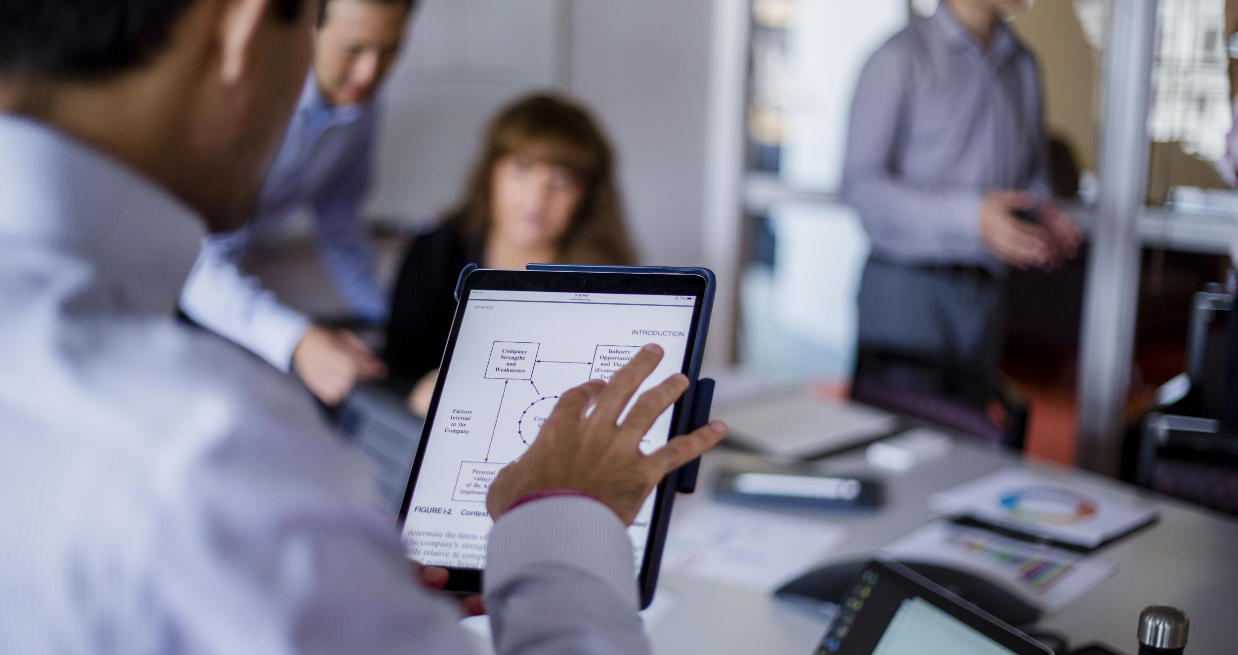 Image of a small meeting, we see over the shoulder of a man holding a tablet, and in the background are 3 other employees.