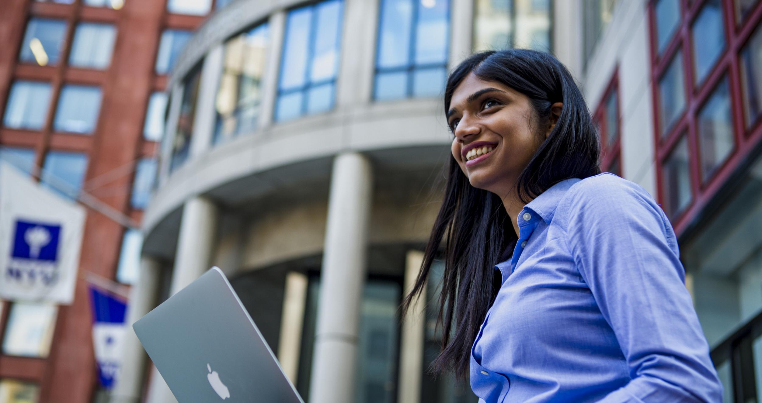 Smiling young woman sitting in front of Stern building with a laptop on her lap
