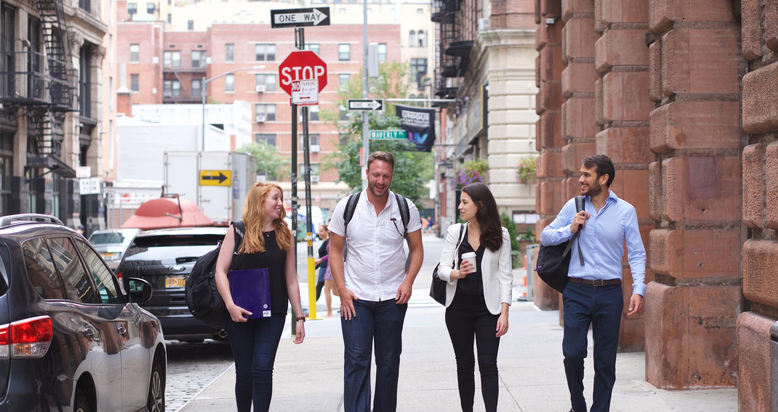 Four people walking down the street