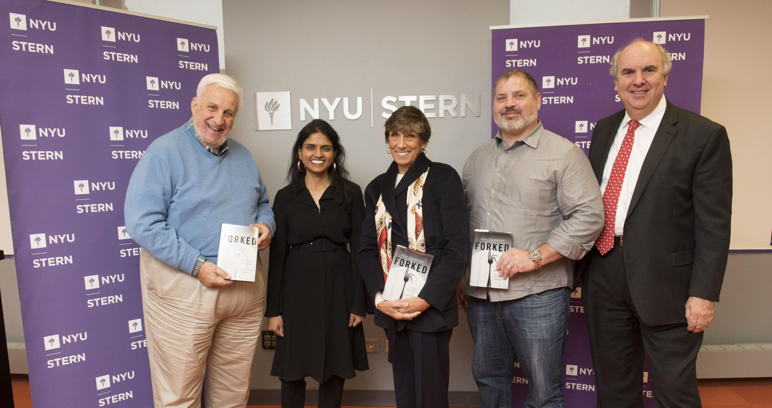 Five people standing in front of a wall with NYU Stern logo, flanked by two purple banners with the NYU Stern logo