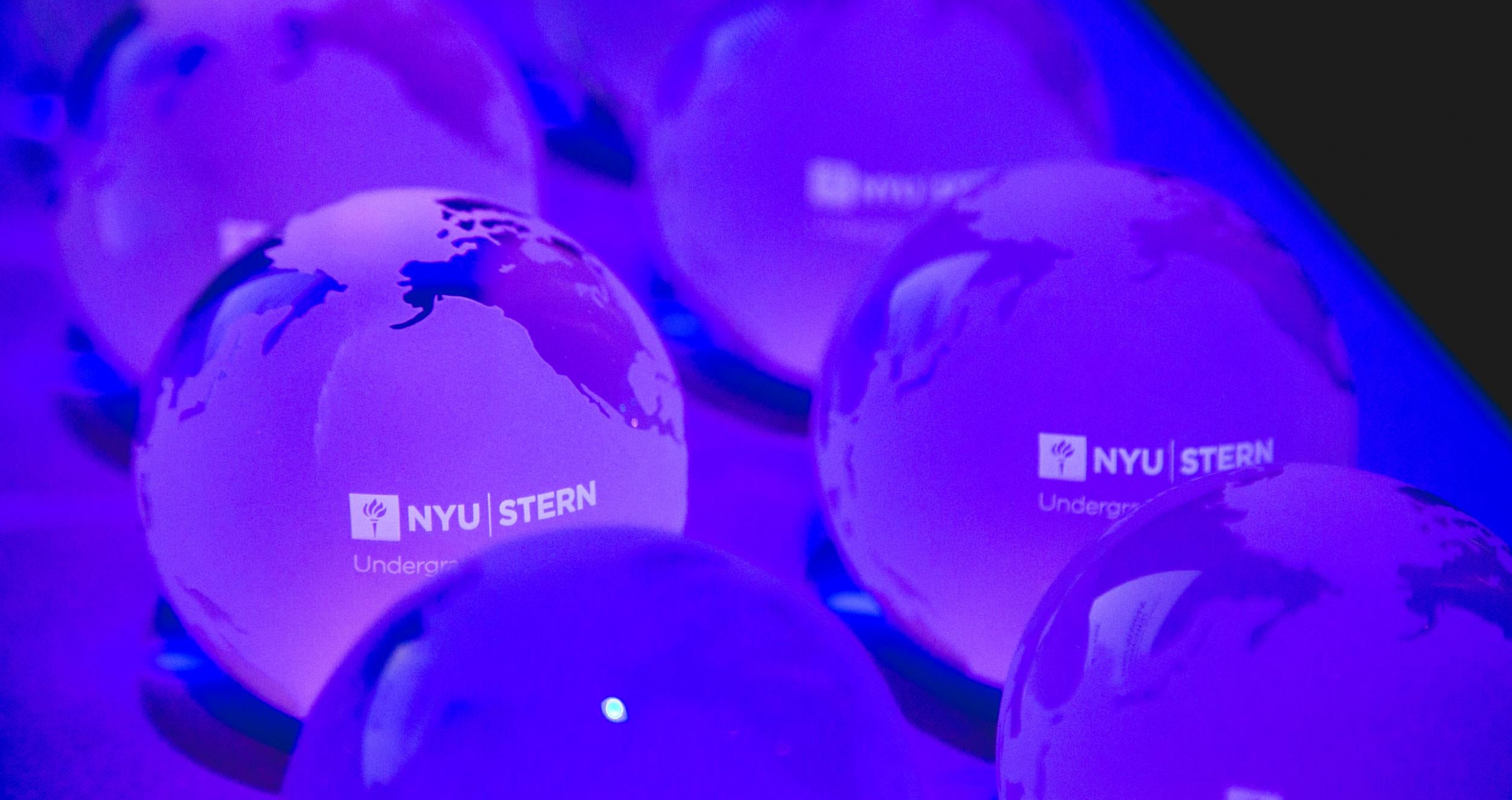 Glass globes with world map and text that says NYU Stern Undergraduate College