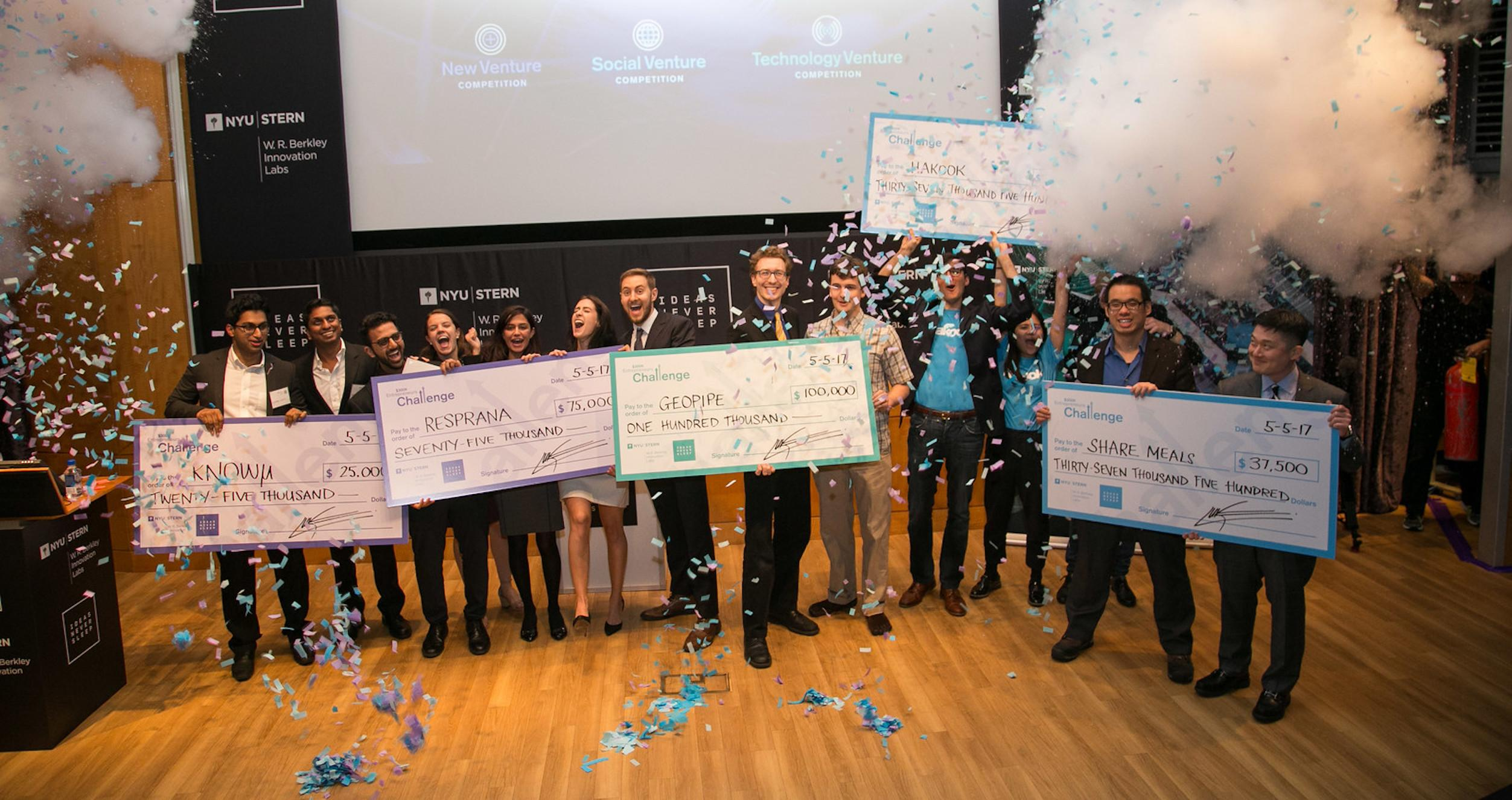 Winners of the $300K Entrepreneurs Challenge holding giant prize checks