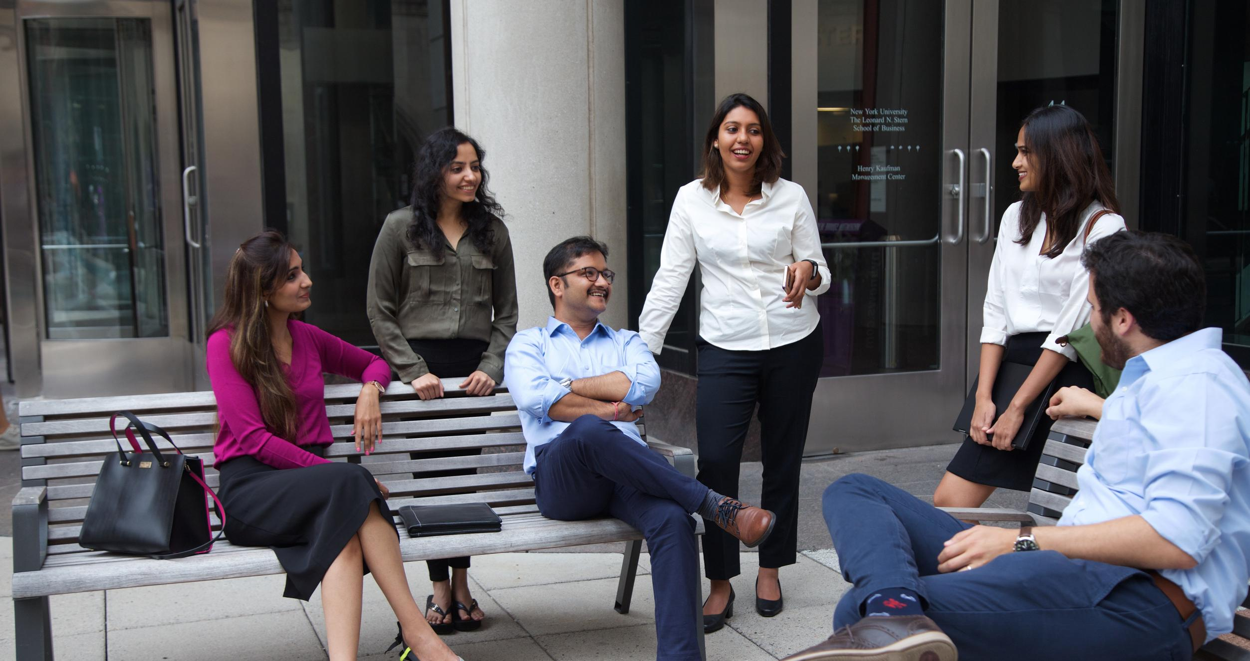Stern students sitting and talking outside of Stern building