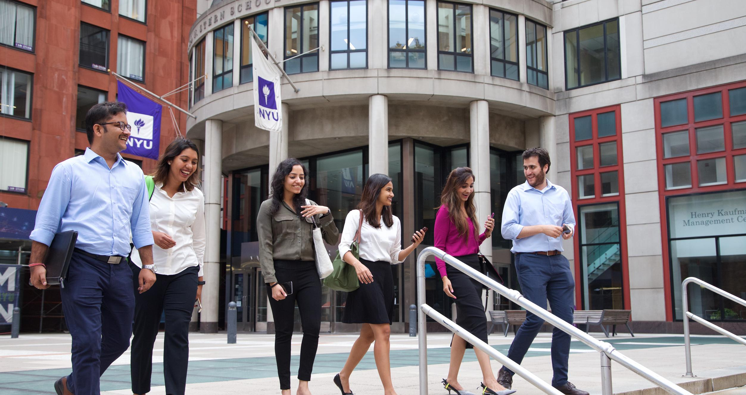 A group of people walking down the steps in front of an NYU building