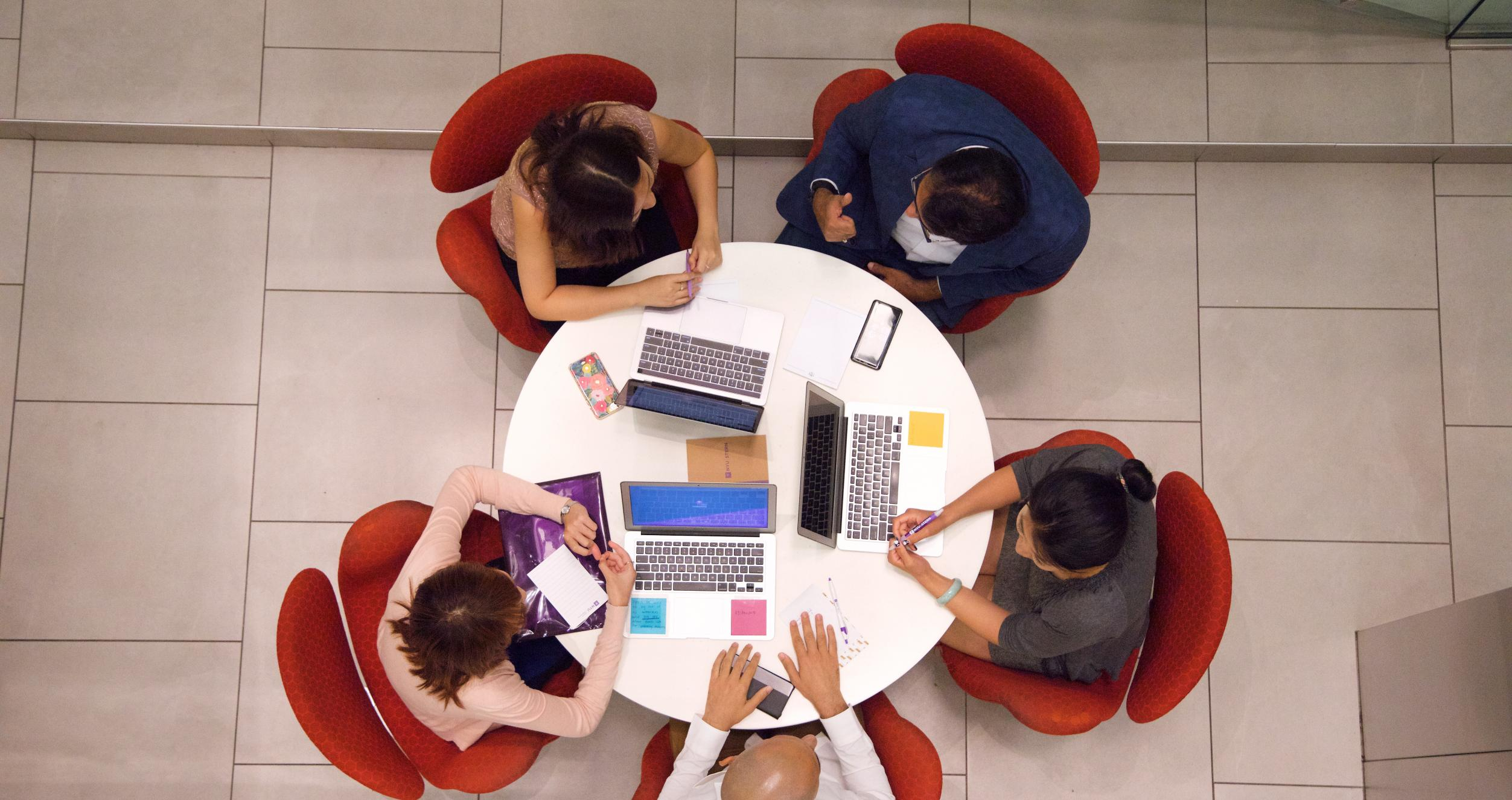 Students around a circular table with laptops