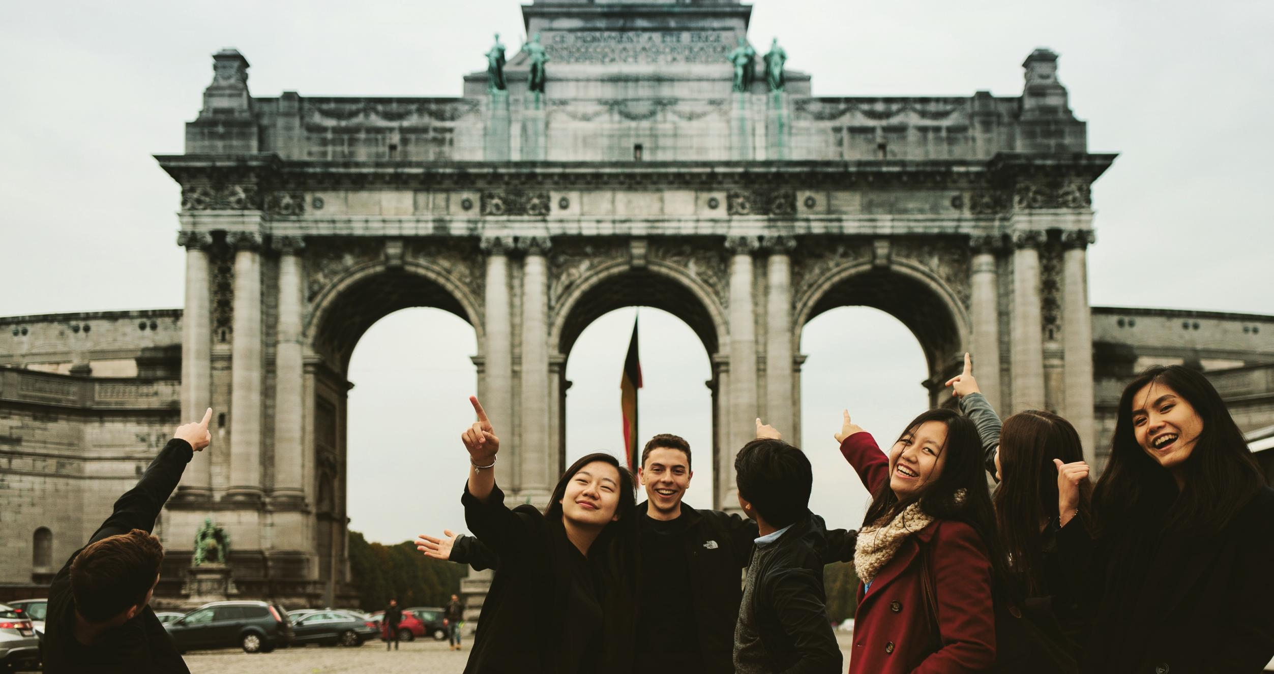 Students pointing to the Arcade du Cinquantenaire on their Brussels, Belgium trip during their semester abroad