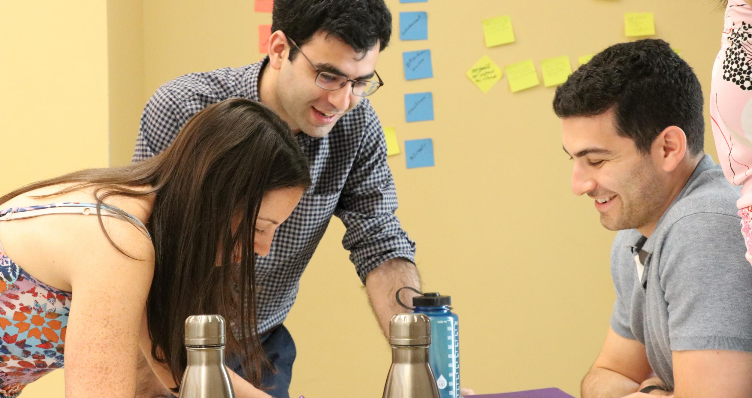 Tech MBA students writing and smiling while solving a problem