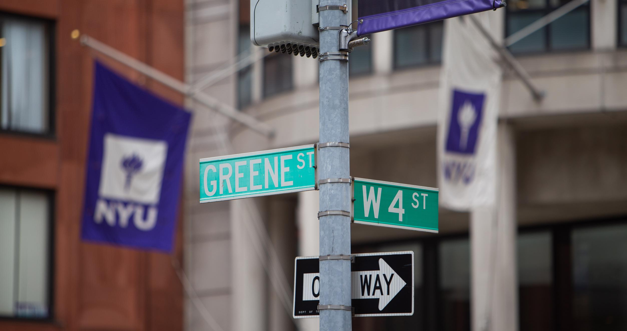 Street signs for Greene St and W 4th with front entrance of KMC in the background